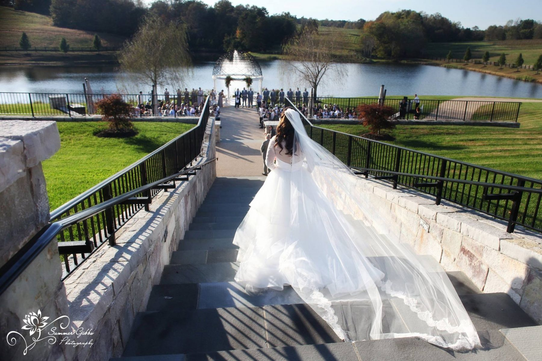 Bride in flowing white dress walks down stone stairs to the Gazebo at Mount Ida Manor