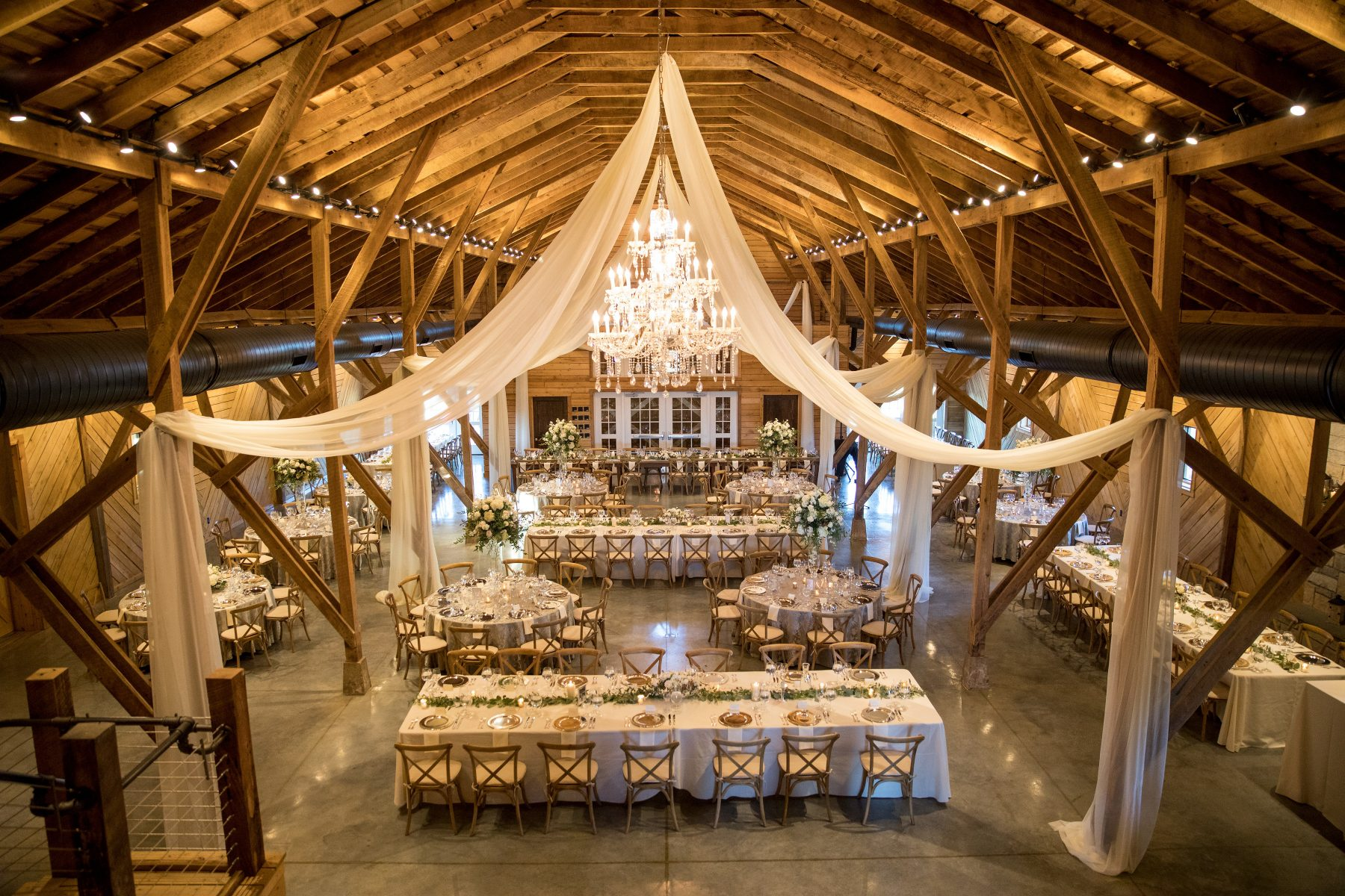Interior of The Lodge at Mount Ida Farm & Vineyard at Mount Ida Reserve decorated for Wedding with white drapes, greenery