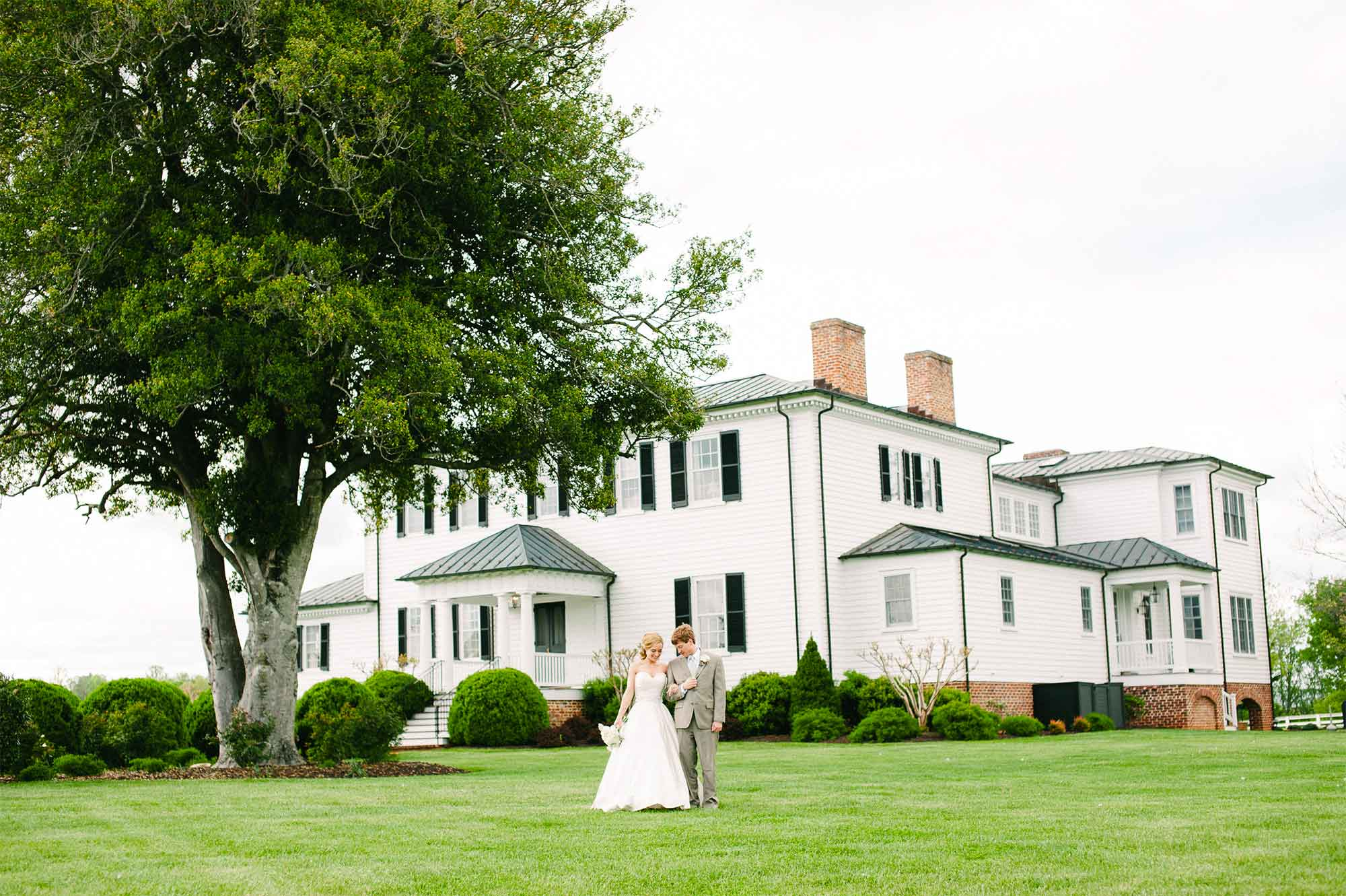 Mount Ida Manor Wedding - Historic Home Wedding Venue - Bride and Groom stand on green lawn in front of stately white Mount Ida Manor in Charlottesville, Virginia