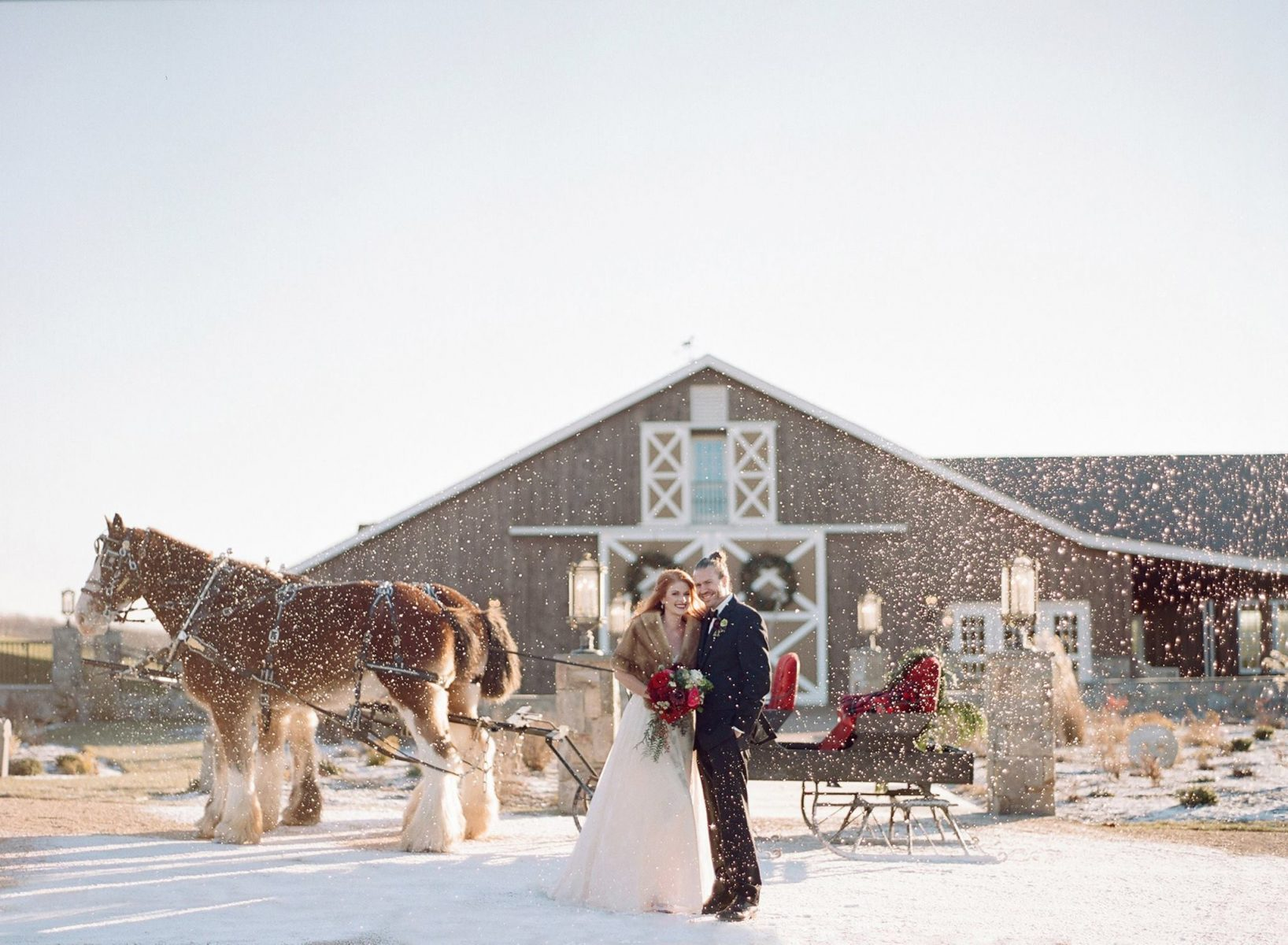 Winter Barn Wedding - The Lodge at Mount Ida Farm & Vineyard - Couple stand in snow with horse and carriage during winter barn wedding